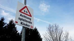 Schild, auf dem Achtung spielende Kinder steht